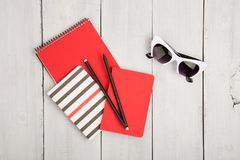Desktop with red and strip notepads, pensils, sunglasses on a wh. Ite wooden background Royalty Free Stock Images