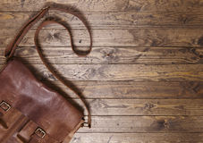 Desktop with satchel. Leather school bag on a distressed wooden background Royalty Free Stock Photo
