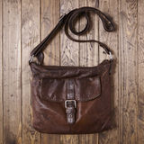 Desktop with satchel. Leather school bag on a distressed wooden background Stock Photos