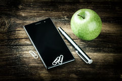 Desktop with smart phone and green apple Stock Photography