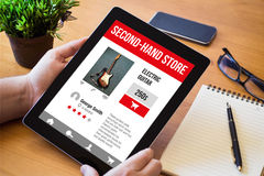 Desktop tablet with second-hand store responsive web. Hands of a man surfing second-hand store resposive website over a wooden workspace table. All screen Royalty Free Stock Photo