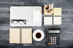 Desktop with various items. Dark wooden desktop with neatly organized laptop, coffee cup, notepad, blank white smartphone, glasses, calculator and other items stock photography