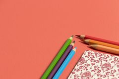 Desktop in vivid coral with notebook in the corner and color pencils royalty free stock images
