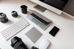 Desktop of the young designer with a laptop with a mouse with a modern professional photo camera with a keyboard with a laptop. Group of objects isolated on a stock photo