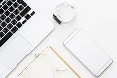 Desktoppunten: laptop, notitieboekje die, hoofdtelefoons, mobiele telefoon, slim horloge op witte achtergrond liggen Vlak leg, ho royalty-vrije stock afbeelding