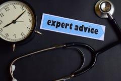 Deskundig Advies op het document met de Inspiratie van het Gezondheidszorgconcept wekker, Zwarte stethoscoop royalty-vrije stock fotografie