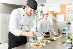 Deskundige Cook Adding Flavor To Schotel in Keuken royalty-vrije stock foto