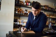 Deskundige die over het aroma, smaakidentificatie, zuurheid schrijven van wijn stock afbeeldingen