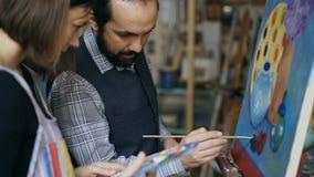 Deskundige kunstenaarsleraar die en grondbeginselen van het schilderen tonen bespreken aan student bij kunst-klasse royalty-vrije stock afbeelding