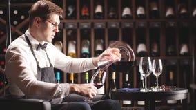 Deskundige overhevelende en gietende wijn in glas Personeel opleiding voor meer sommelier stock videobeelden