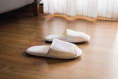 Deslizadores brancos, sapatas no assoalho de madeira na manhã imagem de stock royalty free