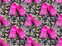Deslizadores de goma rosados del ` s de los niños en los guijarros imagen de archivo