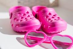 Deslizadores de goma rosados, en el fondo blanco Las sandalias de goma de los ni?os aisladas Zapatos c?modos para la playa imagenes de archivo