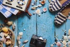 Deslizadores rayados, cámara y decoraciones marítimas en el de madera Fotos de archivo