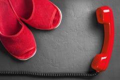Deslizadores vermelhos com o monofone no assoalho foto de stock royalty free