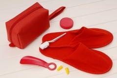 Deslizadores vermelhos, tomadas da orelha, dentes da escova, calçadeira do avião, Fotografia de Stock Royalty Free
