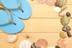 Deslizadores y cáscaras de la playa en la madera Fotos de archivo