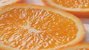 Deslizamento ao longo das fatias das laranjas em um fundo branco e molhado video estoque