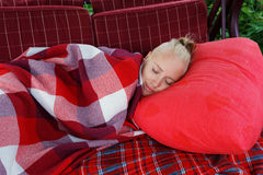Deslizamento da jovem mulher no balanço macio grande no jardim no descanso vermelho coberto pela placa quadriculado vermelha Foto de Stock