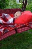 Deslizamento da jovem mulher no descanso vermelho coberto pela placa quadriculado vermelha Fotografia de Stock