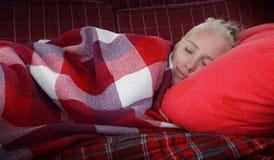 Deslizamento da jovem mulher no descanso vermelho coberto pela placa quadriculado vermelha Imagem de Stock