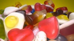 Deslizamiento a través de la pila de fondo de masticación colorido delicioso de los caramelos Dulces coloridos en fondo amarillo almacen de video