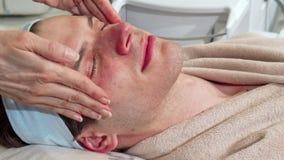 Deslizando o tiro de um homem que relaxa em termas, recebendo a massagem da cara e da cabeça vídeos de arquivo