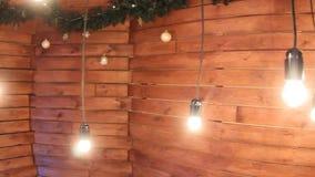 Deslize a câmera Luzes ardentes em fios em um fundo de madeira com bolas e ouropel vídeos de arquivo