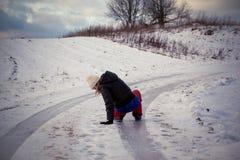 Deslize no gelo e na neve escorregadiços na trilha da estrada no país no dia de inverno de congelação Imagens de Stock