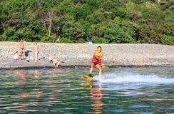 Deslizes do wakeboarder da jovem mulher em uma superfície plana do mar rebocada pelo barco de motor do wakeboard no por do sol imagem de stock royalty free