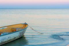 Deslustrado ou tinny pequeno amarrado na praia no crepúsculo com as ondas que dobram na costa foto de stock