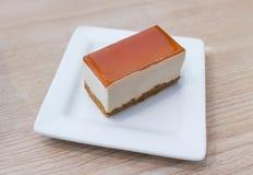 Desmoche del pastel de queso de Nueva York con la porción del caramelo en fondo de madera del vintage de la placa blanca Fotografía de archivo