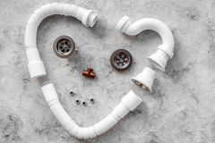 Desmontado cara-como o coração da tubulação de dreno do dissipador deu forma na opinião superior do fundo de pedra cinzento fotos de stock