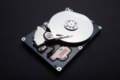 Desmonte o disco rígido do servidor, a superfície magnética e as cabeças de leitura em um fundo preto imagens de stock