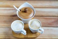 Desnatadoras del café Dos tazas de café en una tabla de madera imagen de archivo