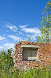 Desolate brick house ruins in the meadow on sunny day Royalty Free Stock Images