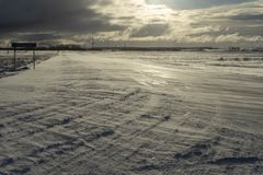 Desolate empty, icy road and harsh sunlight. A desolate empty, icy road lit by harsh sunlight, leading to silhouetted industrial buildings royalty free stock images