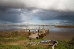 Desolate jetty with fishing boat. An old jetty on an estuary with a deserted fishing boat in the foreground and cloudy skies above Royalty Free Stock Photography