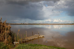 Desolate jetty. An isolated jetty on a reflective estuary an a cloudy day Royalty Free Stock Photography