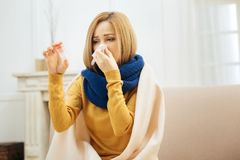 Desolate sick woman holding medication. Being sick. Unhappy unwell young blond woman having fever and blowing her nose and holding medication while having a Stock Photography