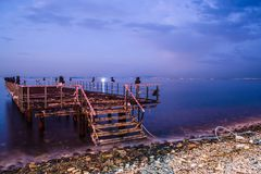 Desolated Dock On Sunset With Calm Sea. A desolated metal constructed dock that used to served as an open air coffee and tea house on top of the sea nearby the royalty free stock images