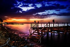 Desolated Dock On Sunset With Calm Sea. A desolated metal constructed dock that used to served as an open air coffee and tea house on top of the sea nearby the stock photography