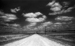 Desolated Gravel Road in the Country with Telephone Lines. And Empty Fields in Day Time with Dark Sky and White Clouds royalty free stock images