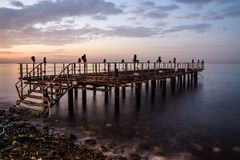 Desolated Dock On Sunset With Calm Sea. A desolated metal constructed dock that used to served as an open air coffee and tea house on top of the sea nearby the stock images