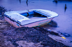 Desolated Rowboat On The Seashore. Surrealist conceptual type of imagery of an old rowboat on desolated area of a shoreline in a small summer town of the country royalty free stock images
