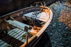Desolated Rowboat On The Seashore. Surrealist conceptual type of imagery of an old rowboat on desolated area of a shoreline in a small summer town of the country royalty free stock photos