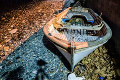 Desolated Rowboat On The Seashore. Surrealist conceptual type of imagery of an old rowboat on desolated area of a shoreline in a small summer town of the country stock image