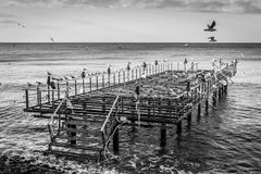 Desolated Steel Construction Pier On Seaside. Desolated steel construction pier on the seaside of a small summer town in winter named Cinarcik which is located stock photo