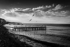Desolated Steel Construction Pier On Seaside. Desolated steel construction pier on the seaside of a small summer town in winter named Cinarcik which is located stock images