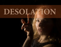 Desolation written on virtual screen. hand of young woman melancholy and sad at the window in the rain. Royalty Free Stock Images